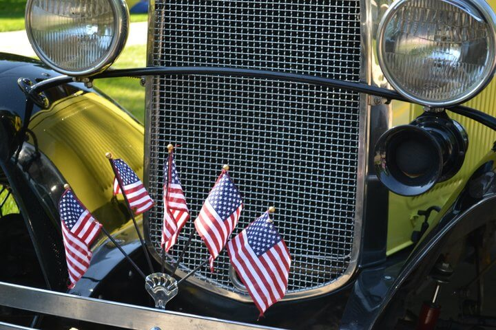 Miniature American flags are mounted on the front bumper of an antique car.