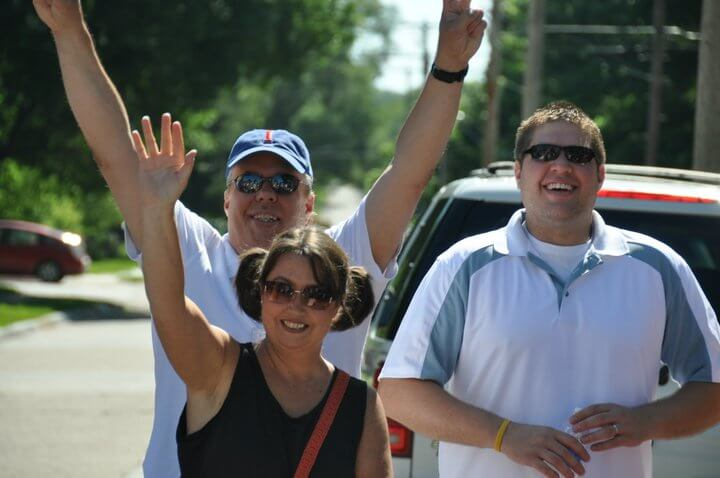Three community members smile and wave at the camera.