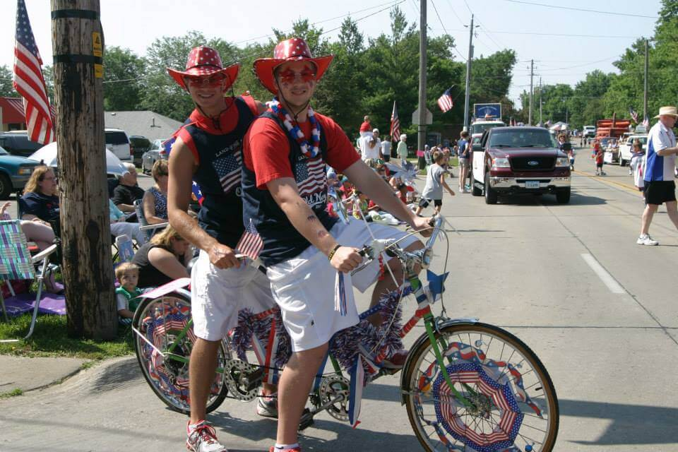 Two parade-goers decked out in patriotic gear ride on a tandem bike.