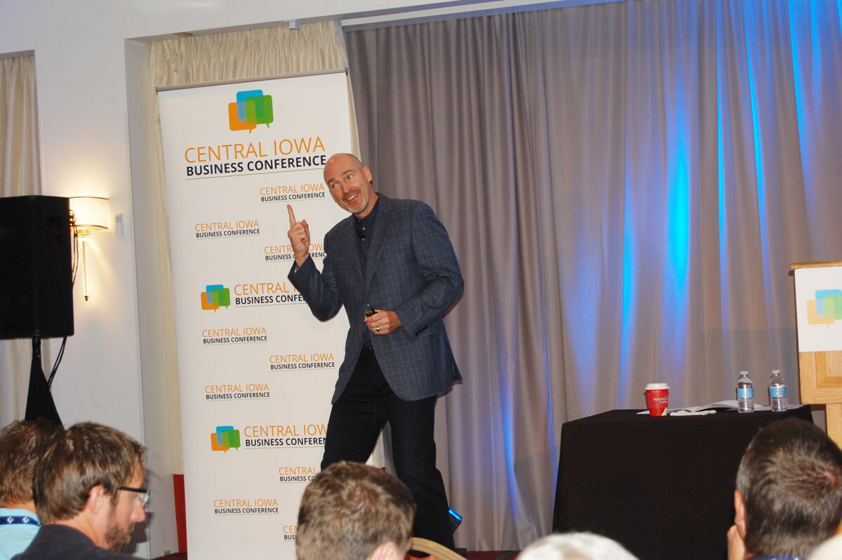 The speaker at a Central Iowa Business Conference gestures on the stage.