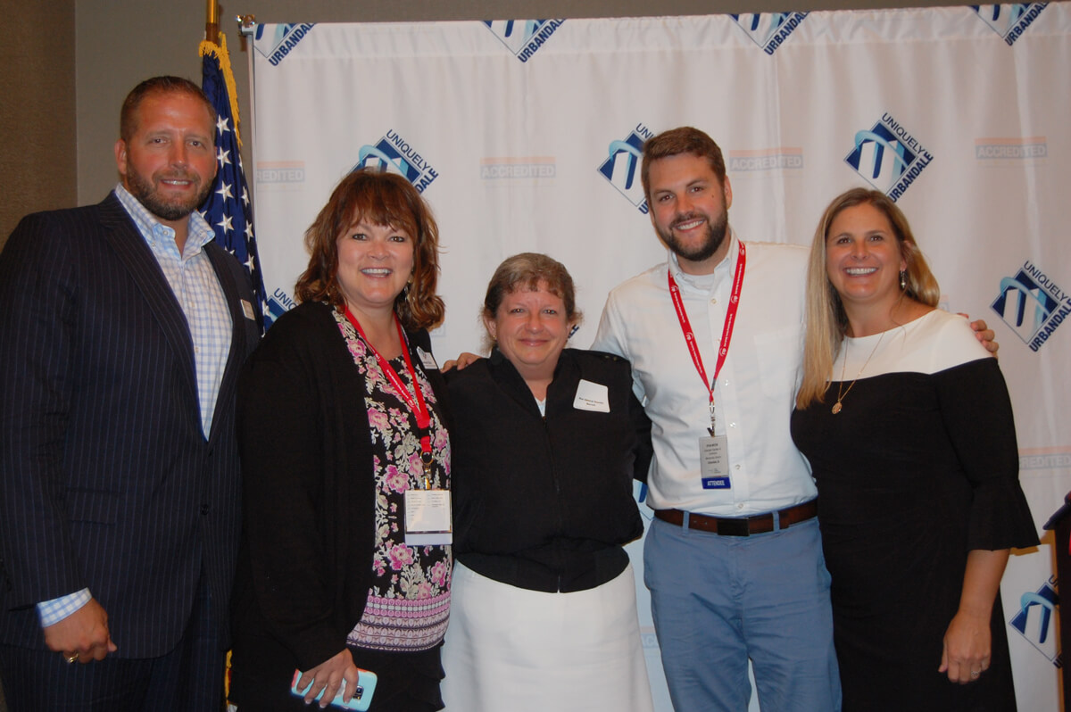 Board members of the Urbandale Chamber smile with the speaker at a luncheon, where the topic was Cyber Security.