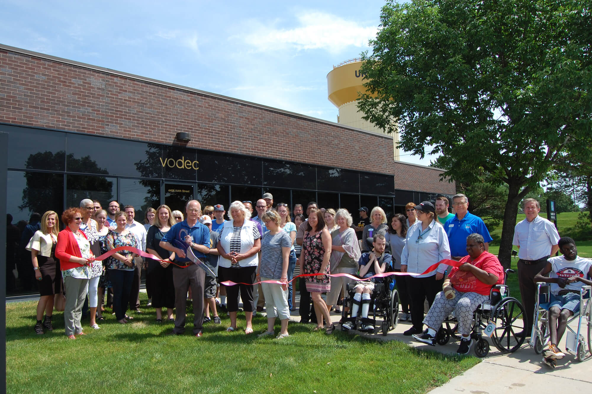 A crowd attends a ribbon cutting ceremony.