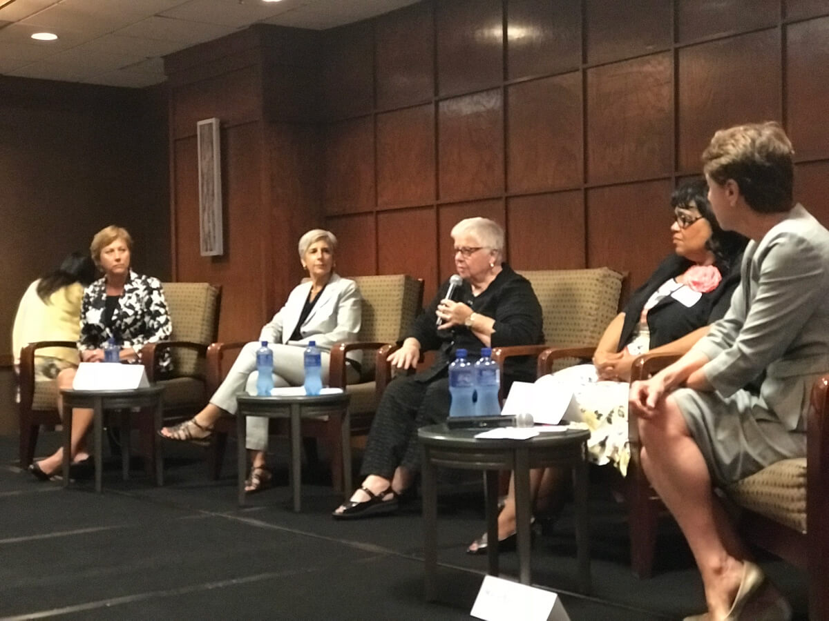 A panel of women engage in discussion.