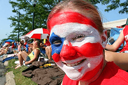 A girl with red and white stripes and a blue star on her face smiles as she watches the parade.