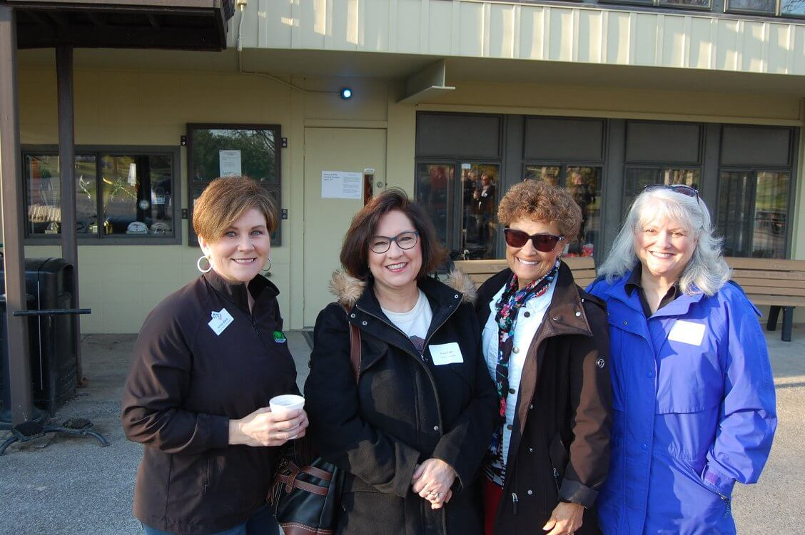 4 Chamber members smile outside of a local business.