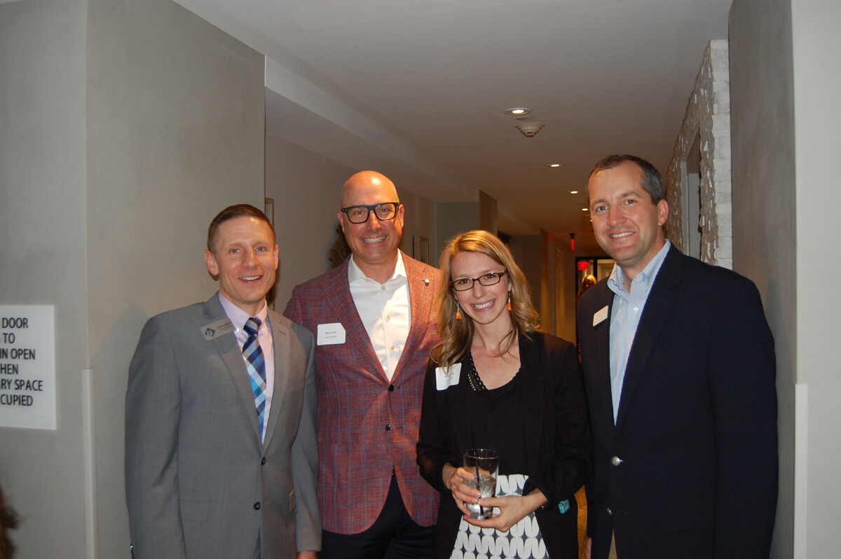 A chamber networking event--members smile in a hallway.