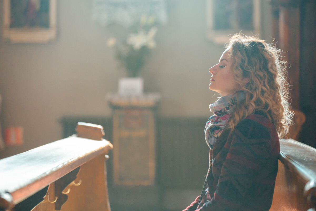 A woman closes her eyes in a church pew.