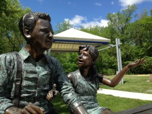 A statue of a man and a little girl in an Urbandale park.