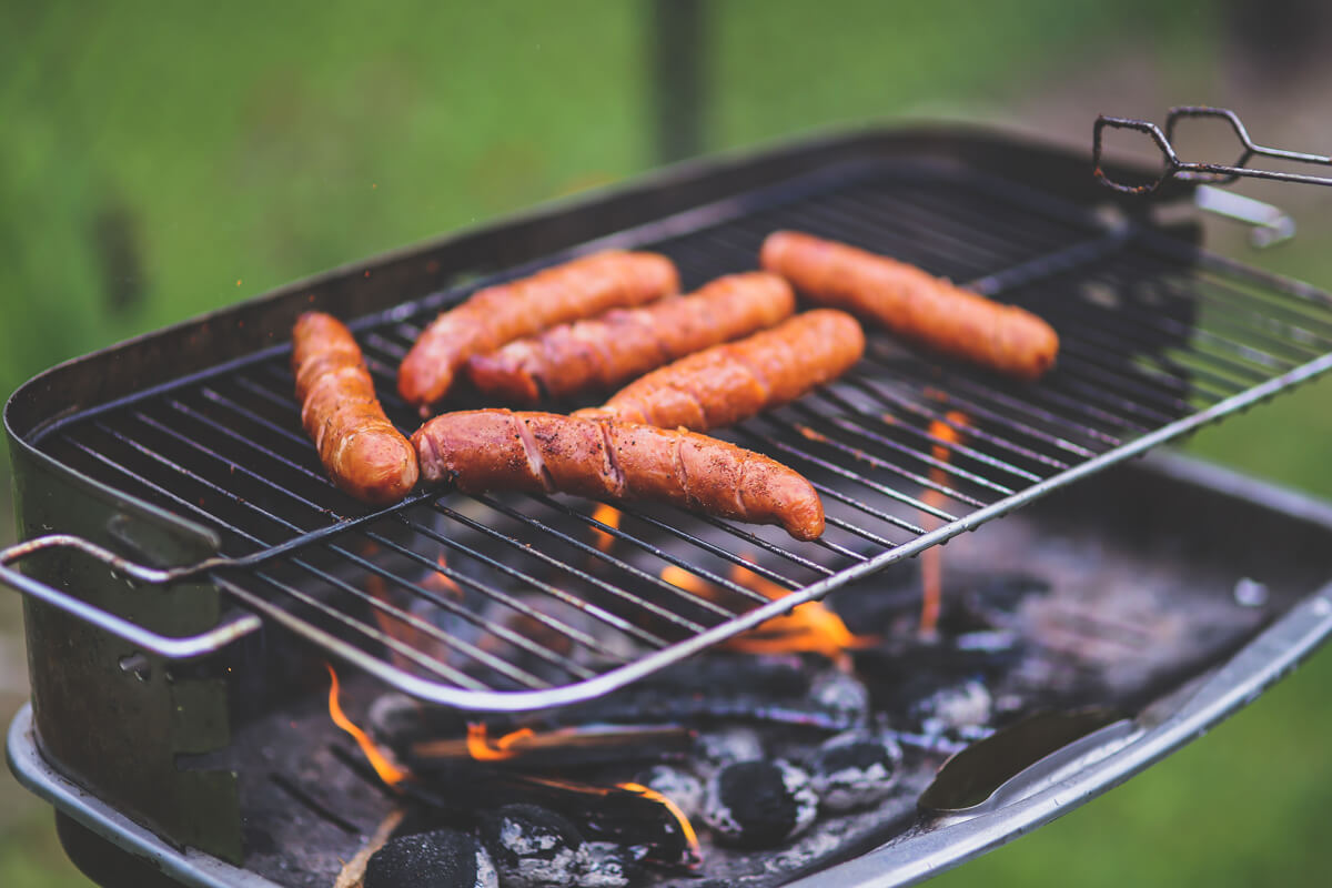 Hot dogs cook on a grill.