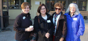 Four female chamber members smile outside a local business.