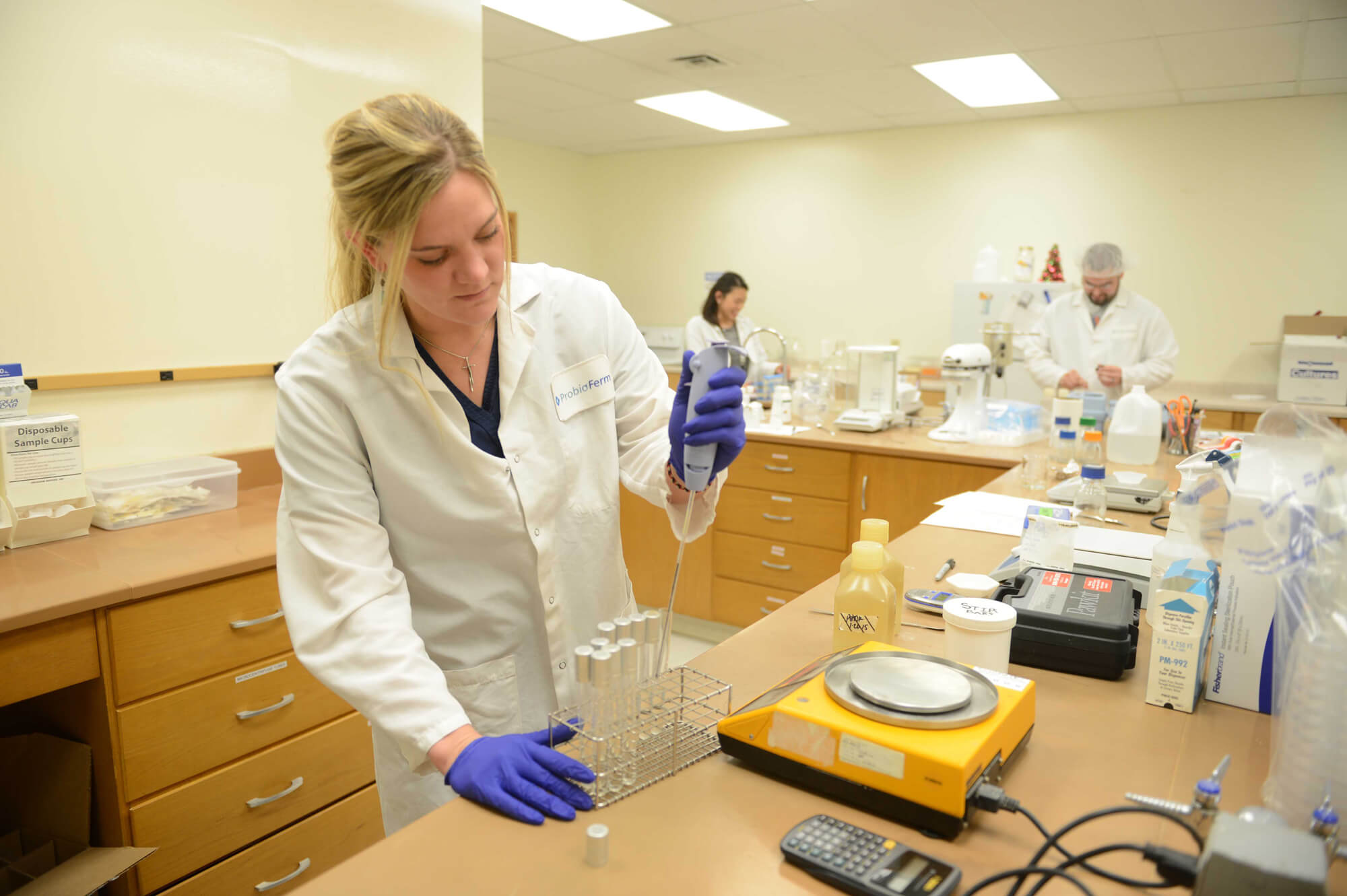 A woman in a lab coat utilizes vials.